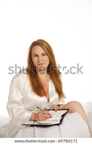 Woman in bed writing in her journal or diary - stock photo