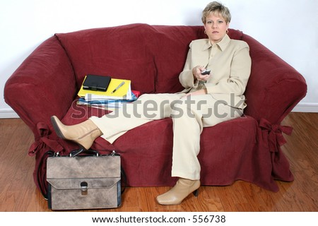 Woman in beige suit with remote, sitting on couch with stack of work papers beside her. - stock photo