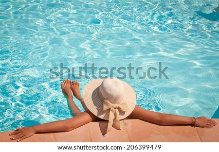 Woman in big straw hat relaxing on the swimming pool. Girl at travel spa resort pool. Summer luxury vacation. - stock photo