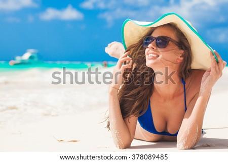 woman in bikini and straw hat having fun on tropical beach - stock photo