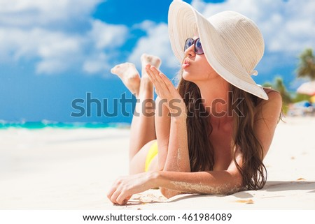 woman in bikini and straw hat relaxing on tropical beach