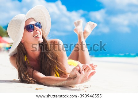 woman in bikini and sun hat relaxing at sunny beach. remote tropical beaches and countries. travel concept
