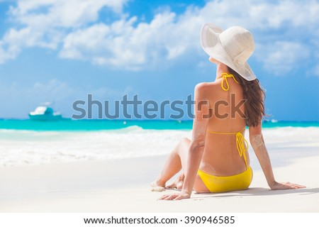 woman in bikini and sun hat relaxing at sunny beach. remote tropical beaches and countries. travel concept - stock photo