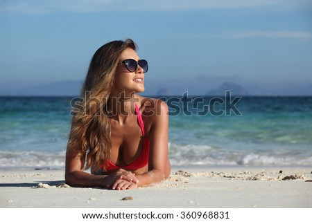 Woman in bikini and sunglasses laying at tropical beach - stock photo