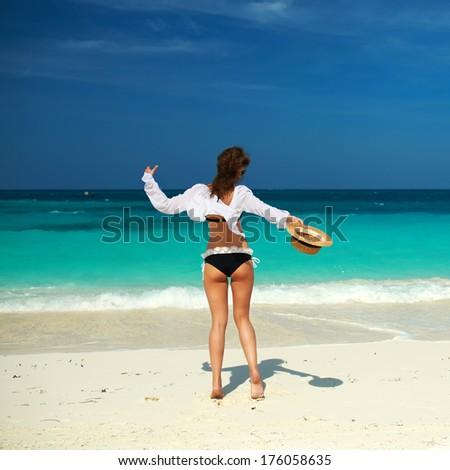 Woman in bikini at tropical beach - stock photo