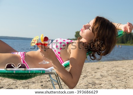 Woman in bikini lounges on beach chair with fruity tropical cocktail drink