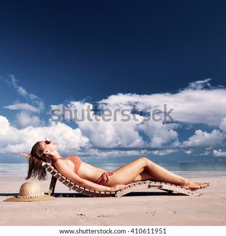 Woman in bikini lying on tropical beach at Seychelles - stock photo