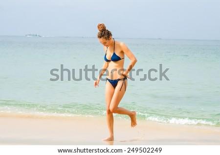 Woman in bikini on the coastline - stock photo