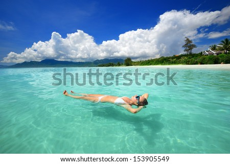 Woman in bikini relaxing lying on the water against the background of the beach and the mountains. - stock photo