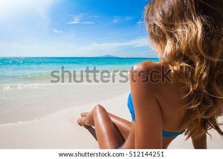 Woman in bikini sitting on the beach at sunny day