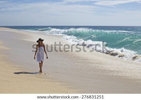 woman in bikini walking alone on the beach in a summer sunny day - stock photo