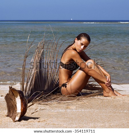 Woman in bikini with palm branch on beach near sea enjoying sun. Long wet hair. Volume curly hairstyle. Tropics. Hot summer day. Sexy girl. Vacation. Photo from Phuket island. Thailand - stock photo