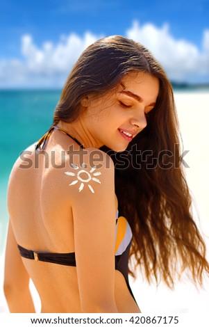 woman in bikini with the drawn sun on a shoulder at beach - stock photo