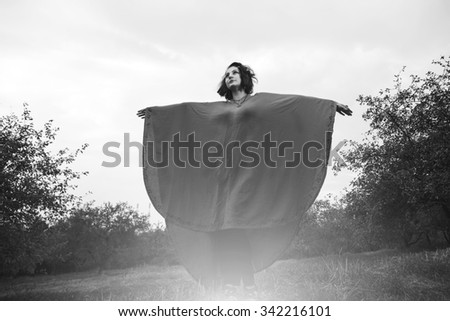 Woman in black and white. Girl - the hippie style. Evening walk. Young girl on a background of light flashes. Magic, magical, fairy tale. Mysterious witch woman. Freedom, enjoyment, lifestyle. - stock photo