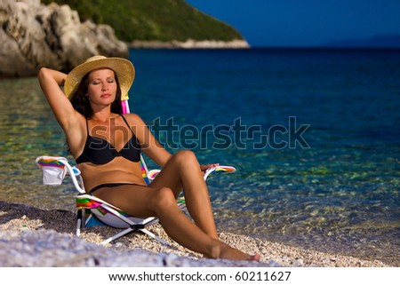 Woman in black bikini and straw hat tans on deckchair in beauty bay