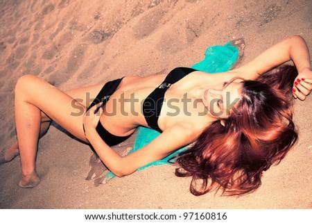 woman in black bikini on sand beach, retro style colors, small amount of grain added, full body shot - stock photo