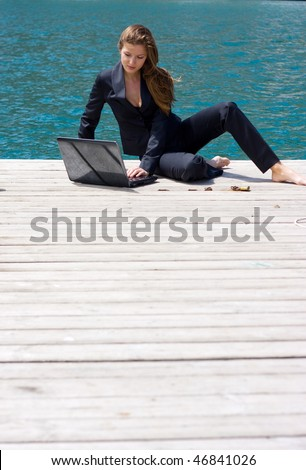 woman in black business suit sitting with laptop near the sea - stock photo