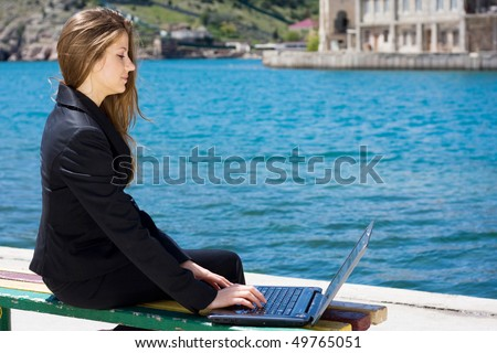 woman in black business suit with laptop sitting near the sea - stock photo