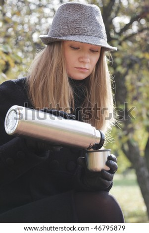 Woman in black coat and hat filling cup from thermos