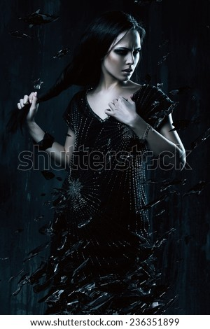 woman in black dress holding hair with broken glass in dark - stock photo
