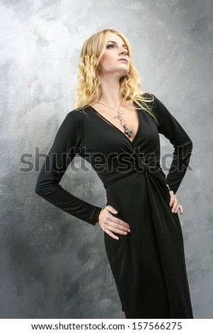 Woman in black dress on grey background