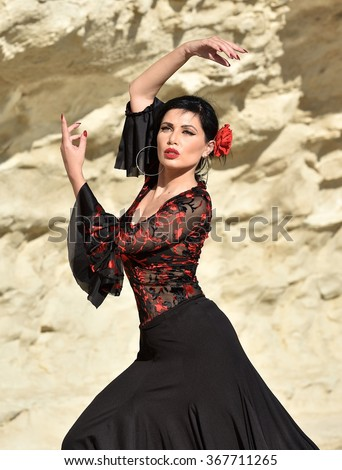 Woman in black dress stay in dancing pose.Portrait of Flamenco dancer in yellow rock background. Photo of flamenco dancer. Beautiful brunette woman, flamenco dancer in natural background.Dancing woman - stock photo