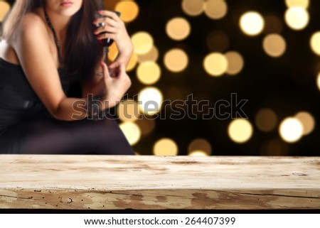 woman in black dress with glass of red wine and free space of wooden desk and night