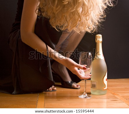 woman in black evening dress holding full glass of Champagne - stock photo