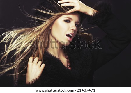 Woman in black fur hat and coat - on black background - stock photo