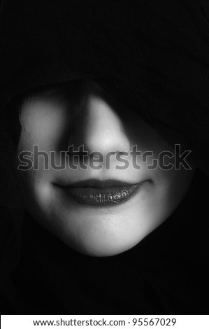 Woman in black hood in black and white - stock photo