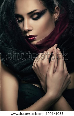 woman in black hood with closed eyes - stock photo
