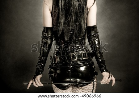 woman in black latex corset, with horsewhip in hands - stock photo