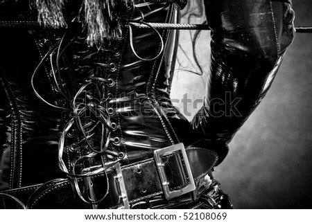 woman in black latex uniform - corset, with horsewhip - stock photo