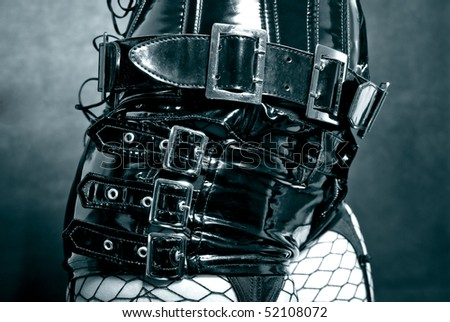 woman in black latex uniform - corset with metal buckles - stock photo