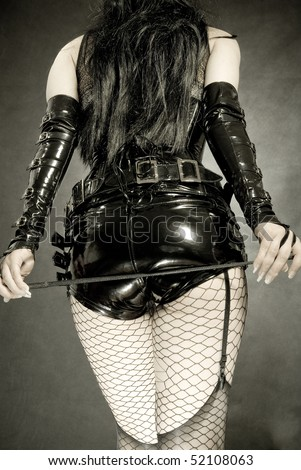woman in black latex uniform, shorts and corset, with horsewhip in hands - stock photo