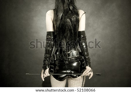 woman in black latex uniform with horsewhip in hands, back - stock photo