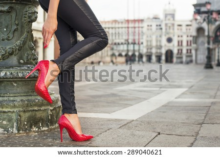 Woman in black leather pants and red high heel shoes - stock photo