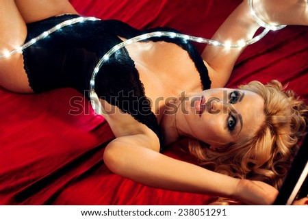 Woman in black lingerie with fairy lights laying on bed in darkness - stock photo