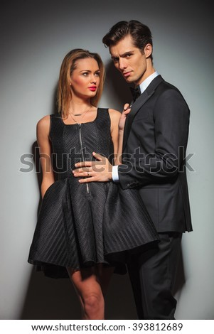 woman in black with legs crossed pulling man's jacket while looking away from the camera. businessman touching woman's dress while looking at the camera in gray studio background - stock photo