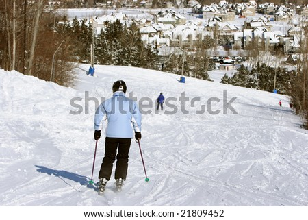 Woman in blue and white skiing down a hill on a sunny winter's day.