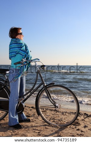woman in blue, bike and shawl at sea shore