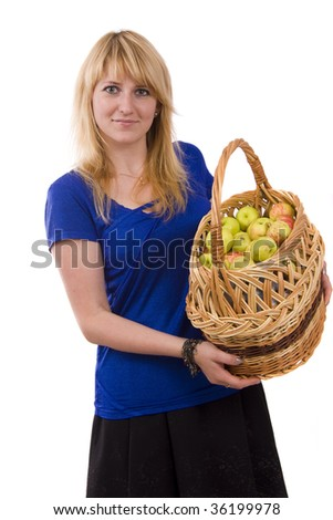 Woman in blue blouse standing and holding a basket full apples on white background. Beautiful girl holding a basket of delicious fresh fruits. Pretty girl with basket of apples. Isolated over white - stock photo