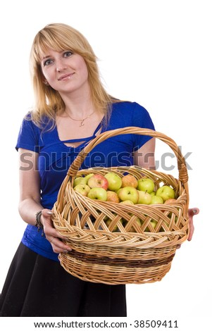 Woman in blue blouse standing and holding a basket full apples on white background. Beautiful girl holding a basket of delicious fresh fruits. Pretty girl with basket of apples. Isolated over white. - stock photo
