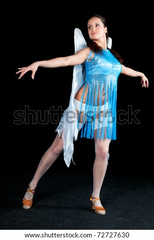 Woman in blue dress dancing on a black background