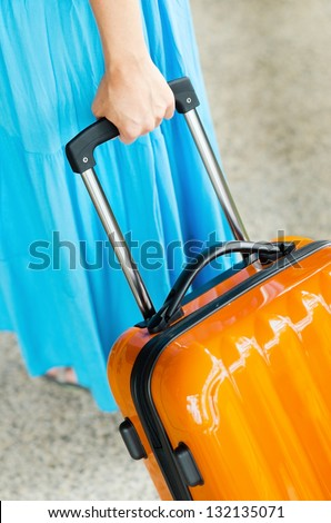 Woman in blue dress holds orange suitcase in hand.