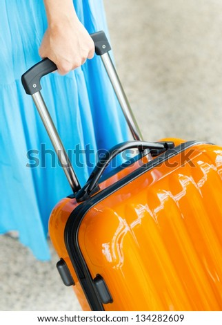 Woman in blue dress holds orange suitcase in hand. - stock photo