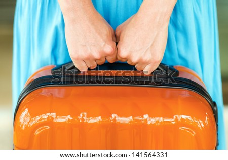 Woman in blue dress holds orange suitcase in hands. - stock photo
