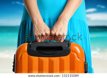 Woman in blue dress holds orange suitcase in hands on the beach background. - stock photo