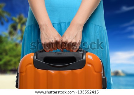 Woman in blue dress holds orange suitcase in hands on tropical landscape background.