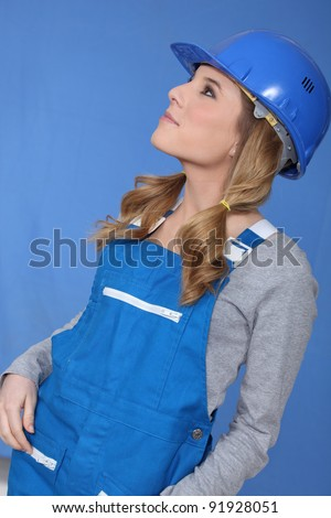 Woman in blue overalls and hardhat - stock photo